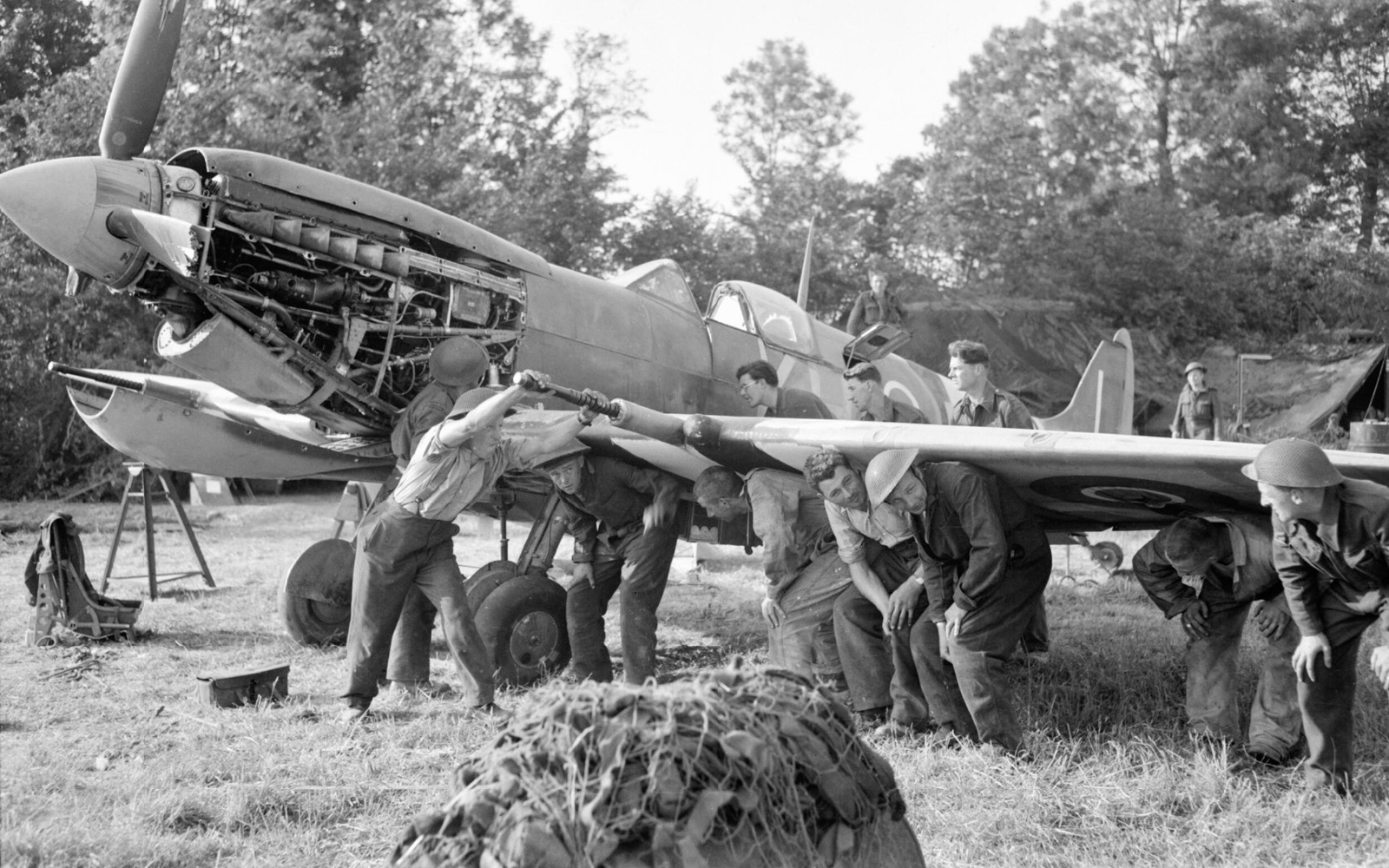 Men of an RAF Repair and Salvage Unit working on a damaged Supermarine Spitfire Mk IX of No 403 Squadron, Royal Canadian Air Force, at a forward airstrip in Normandy, 19 June 1944