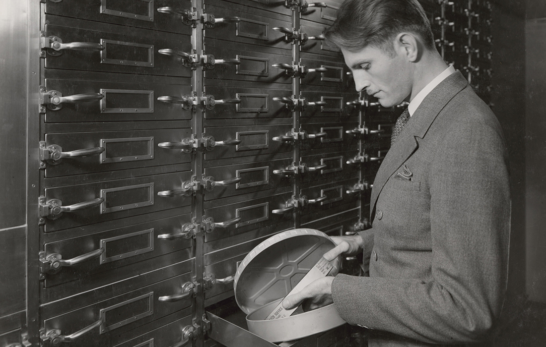 The sound engineer, Glenn C. Henry, holds a reel of motion picture film from the archive, 1937
