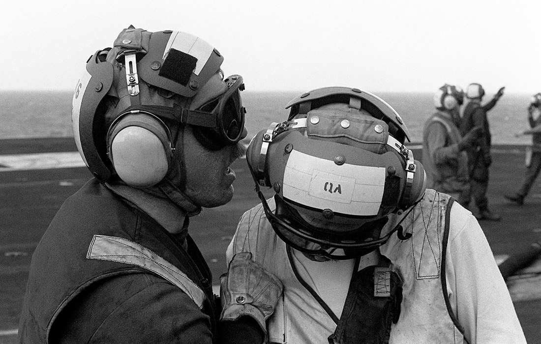 A flight deck crew member attempts to communicate with a companion despite the plane engine noise aboard the aircraft carrier USS JOHN F. KENNEDY (CV-67)