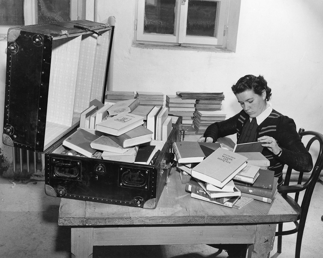 The librarian carefully enters the consignment into her books, 1952