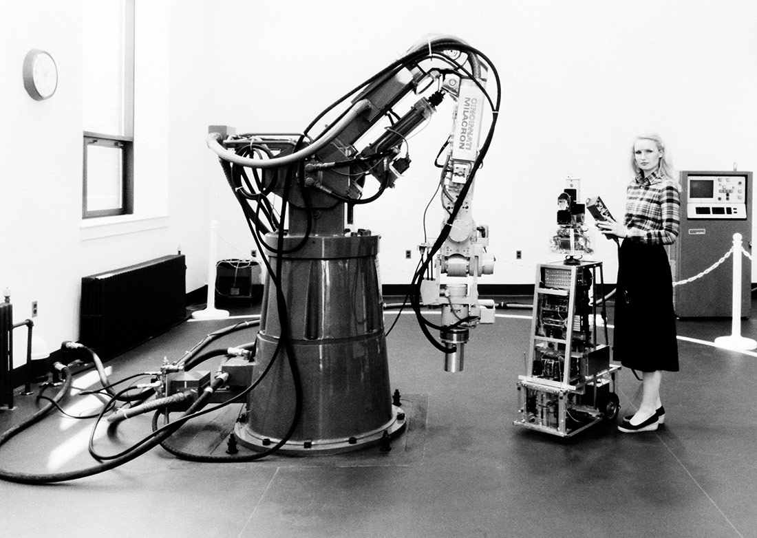 Sharon Hogge, an electronics engineer, poses with autonomous sentry robot ROBART I and the HT3 Industrial Robot. Maryland, 1983