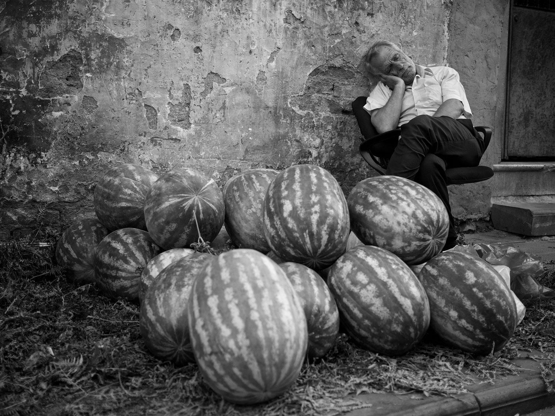 Home dormint al costat d'uns melons a Istanbul, Turquia.