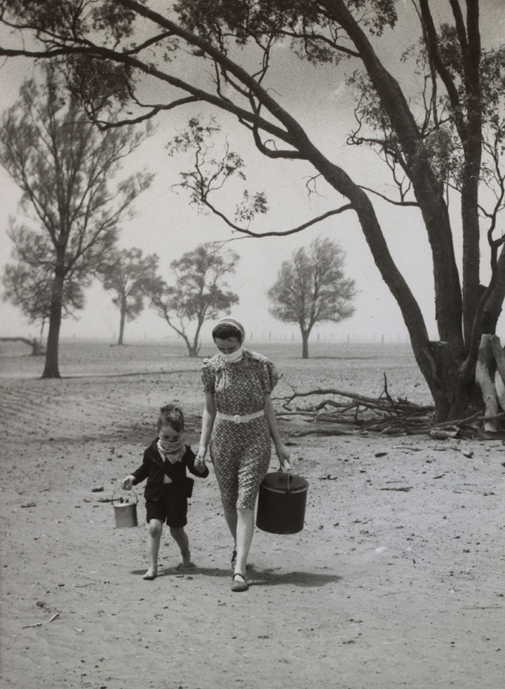 Mrs Dunn and her son, Colin, cross a barren, dusty paddock. Wimmera, 1940.