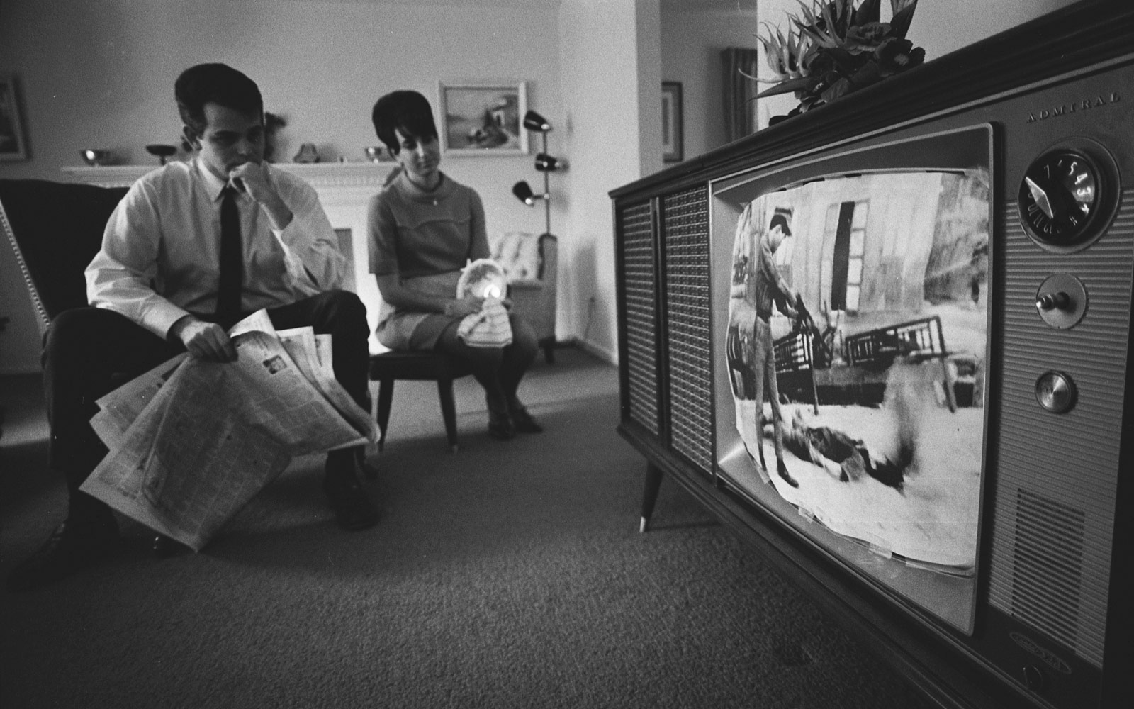 A man and a woman watching a film footage of the Vietnam war on a television, 1968